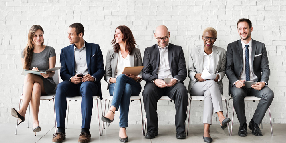 Six professionals sitting on chairs smiling. Aviso Wealth Financial Services